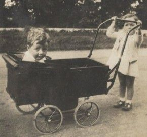 1930s child pushing little brother in pram