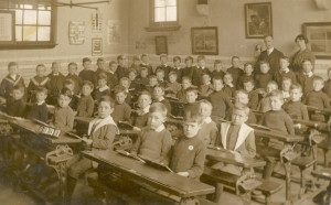 Victorian classroom. Children sat at desks in rows facing the teacher.
