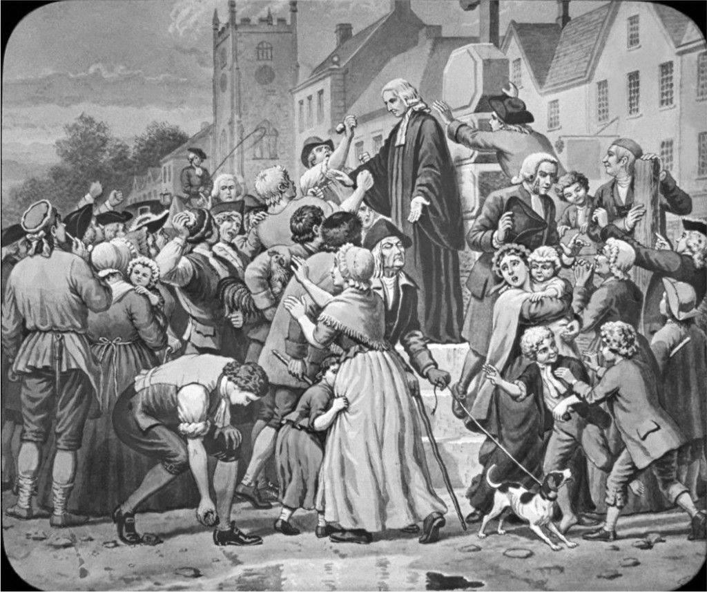 John Wesley, founder of the Wesleyan Church, preaching to a large, boisterous crowd
