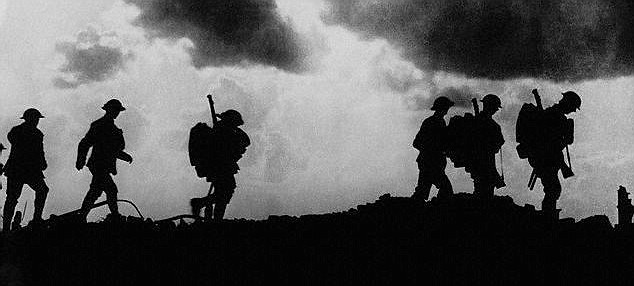 British troops in silhouette march towards trenches near Ypres at the Western Front during the First World War.